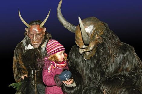 Homens fantasiados de Krampus com criança no colo (Fonte: http://persephonemagazine.com/2011/12/holy-holiday-hell-the-krampus/)