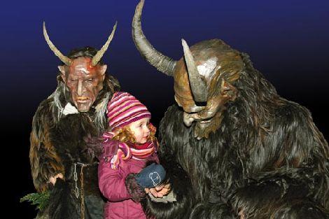 Homens fantasiados de Krampus com criança no colo (Fonte: http://persephonemagazine.com/2011/12/holy-holiday-hell-the-krampus/)